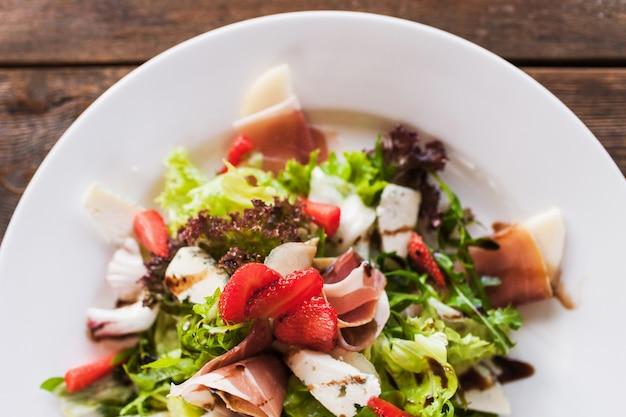 Insalata verde fresca con prosciutto di parma, formaggio blu e fragola che serve nel ristorante sulla tavola di legno.