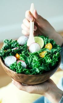 Insalata verde fresca in una ciotola di legno.
