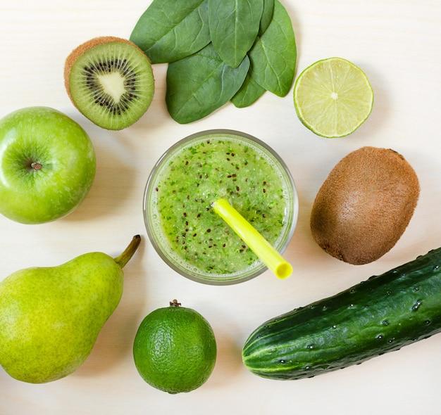 Frullato verde fresco nel bicchiere e frutta e verdura.