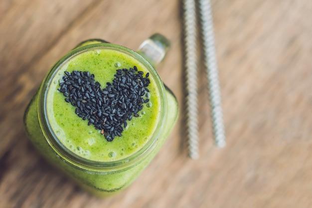 Frullato verde fresco con banana e spinaci con cuore di semi di sesamo. amore per un concetto di cibo crudo sano