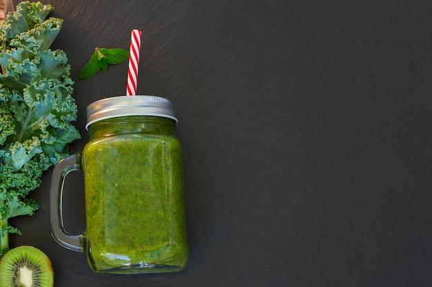 Bevanda frullata verde fresca sul nero con ingredienti