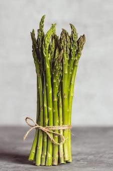 Asparagi verdi freschi della sorgente su un fondo di legno. stagione degli asparagi