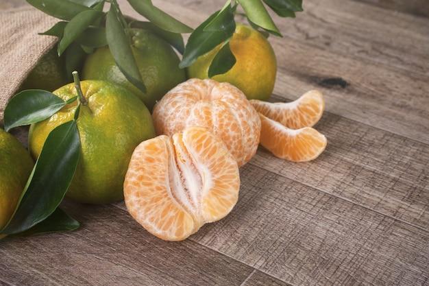 Mandarino mandarino verde fresco con foglie fresche sul concetto di raccolto di sfondo tavolo in legno scuro.
