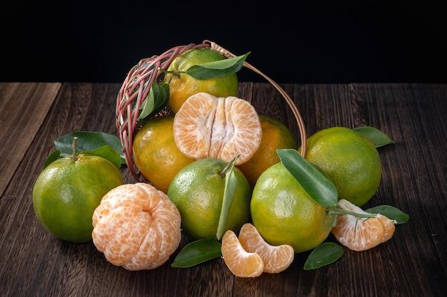 Mandarino verde fresco del mandarino con le foglie fresche sul concetto del raccolto del fondo della tavola di legno scuro.