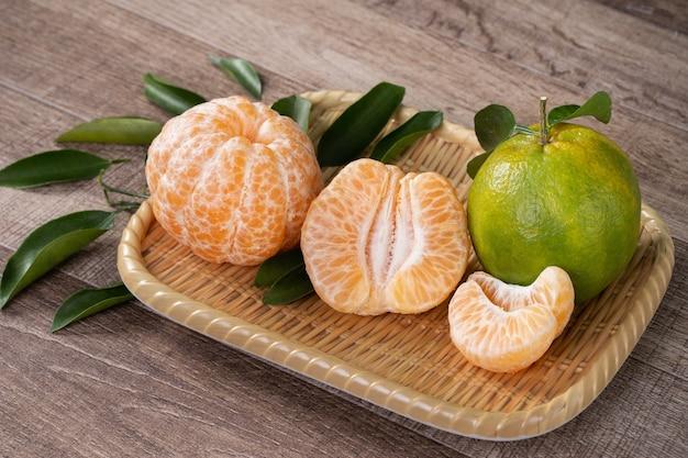 Mandarino mandarino verde fresco con foglie fresche sul concetto di raccolta tavolo in legno scuro.