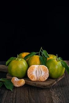 Mandarino verde fresco mandarino con foglie fresche su tavolo in legno scuro con concetto di raccolta sfondo nero.