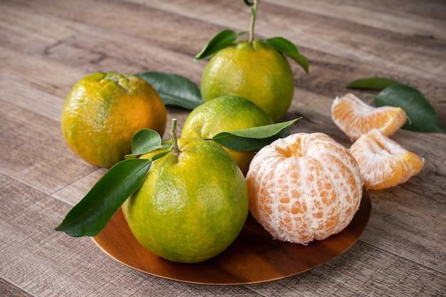 Mandarino mandarino verde fresco con foglie fresche.