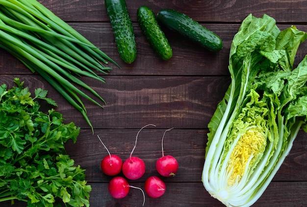 Verdure verdi fresche (cavolo, cetrioli), cipolle verdi, prezzemolo e ravanello su fondo di legno. per le insalate. vista dall'alto
