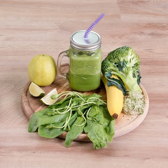 Verdure verdi fresche, frutta e frullato verde in vaso