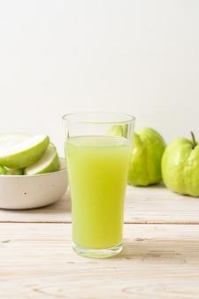 Bicchiere di succo di guava fresco con frutta guava fresca sul tavolo di legno