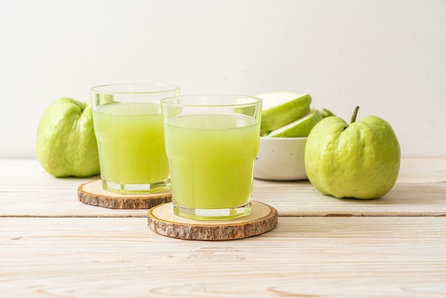 Bicchiere di succo di guava fresco con frutta fresca di guava sul tavolo di legno