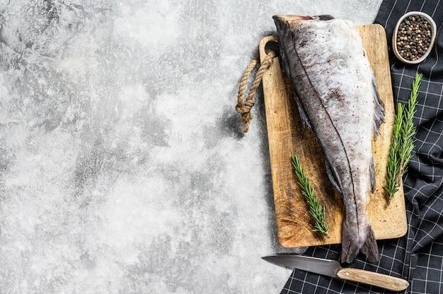 Carcassa di pesce fresco eglefino sul tagliere
