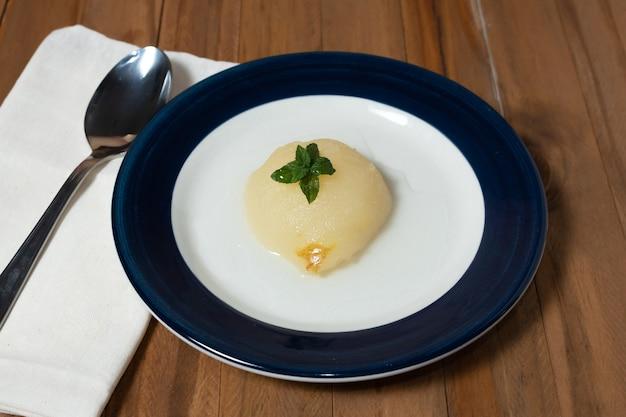 Pere mezze fresche servite con sciroppo dolce. sfondo di tavolo in legno.