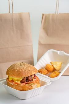 Hamburger fresco nell'imballaggio di eco, alimenti a rapida preparazione, fondo bianco isolato. consegna di hamburger, hamburger