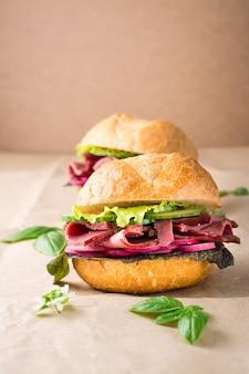 Hamburger fresco con pastrami, cetriolo, ravanello ed erbe aromatiche su carta artigianale. fast food americano.. copia spazio
