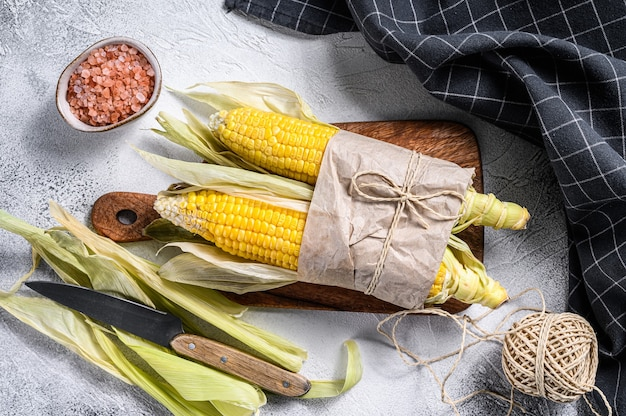Pannocchia di mais raccolto fresco sul mercato contadino, verdure locali. sfondo grigio.