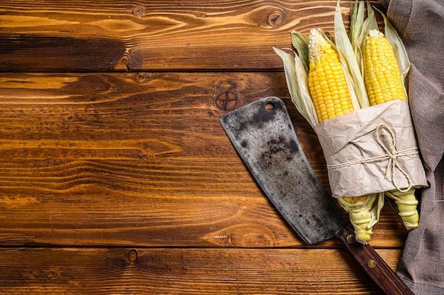 Pannocchia di mais raccolto fresco sul mercato contadino, verdure locali. fondo in legno. vista dall'alto.