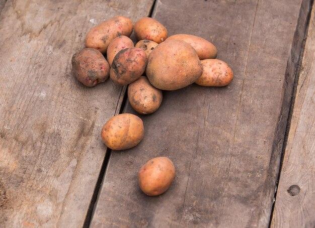 Patate fresche raccolte con terreno ancora sulla pelle, su una tavolozza di legno grezzo.