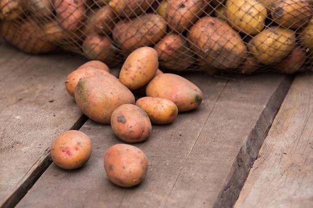 Patate fresche raccolte con terra ancora sulla pelle, che fuoriescono da un sacchetto di tela da imballaggio, su una tavolozza di legno ruvida.