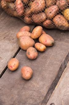 Patate fresche raccolte con terreno ancora sulla pelle, che fuoriescono da un sacchetto di tela da imballaggio, su una tavolozza di legno ruvida.