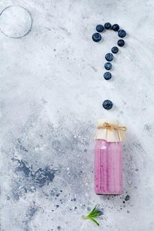 Frullato di mirtilli freschi sani bacche e menta in un barattolo di vetro su fondo di cemento bianco chiaro.