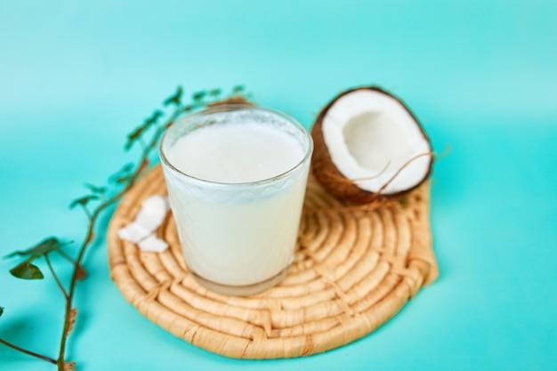 Latte di cocco sano fresco in un bicchiere sulla superficie blu