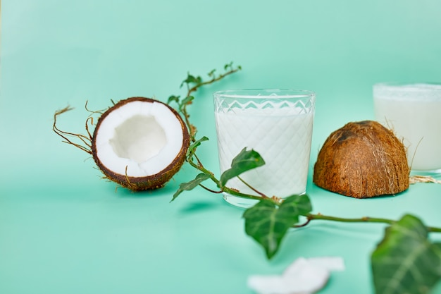 Latte di cocco sano fresco in un bicchiere sulla superficie verde