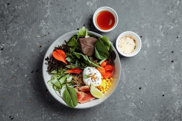 Fresco e salutare colazione leggera, pranzo di lavoro. colazione con uovo in camicia, grano saraceno, pesce rosso, insalata fresca, cetrioli e pomodorini, concetto di pranzo di lavoro.
