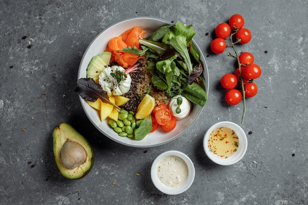 Colazione leggera e sana, pranzo di lavoro. colazione con uovo in camicia, grano saraceno, pesce rosso, insalata fresca, cetrioli e pomodorini, concetto di pranzo di lavoro.