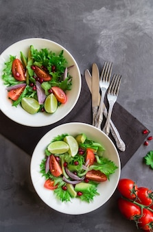 Insalata sana fresca con pomodori, avocado e melograno in ciotole su superficie di cemento grigio. vista dall'alto.