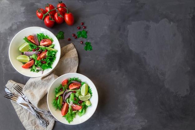 Insalata sana fresca con pomodori, avocado e melograno in ciotole su cemento grigio
