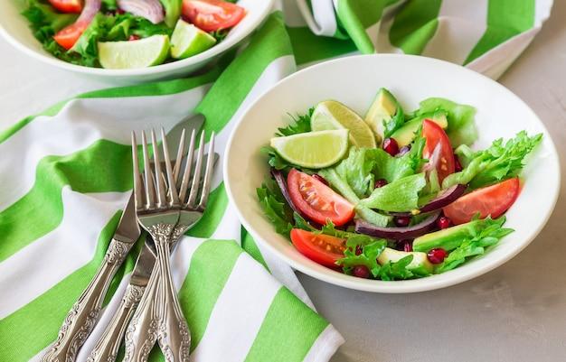 Insalata fresca e sana con pomodori, avocado e melograno in ciotole su fondo di cemento chiaro.