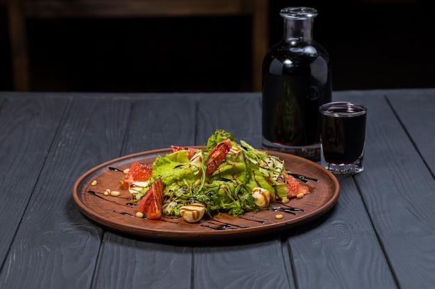 Insalata sana fresca con vino sulla tavola di legno nera