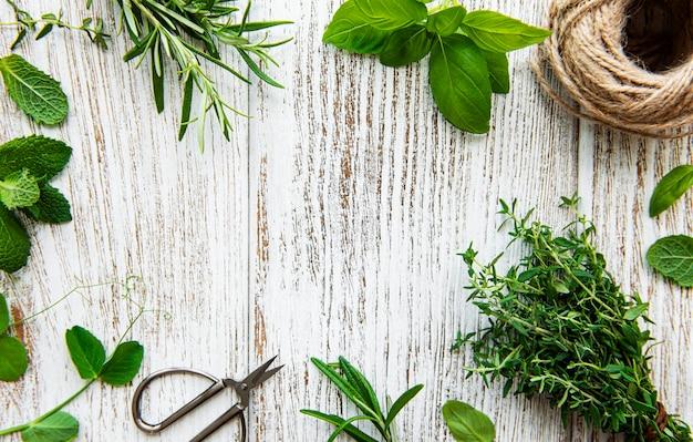 Erbe aromatiche fresche e spago sulla vista superiore del fondo di legno