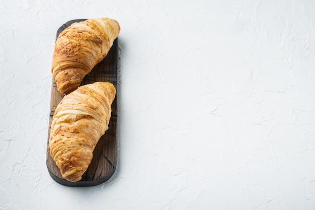 Set croissant marrone dorato al forno fresco fatto in casa, su pietra bianca