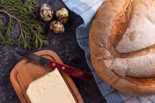 Pane fresco fatto in casa con burro su una superficie scura