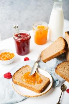 Pane fresco fatto in casa con marmellata e latte, cibo semplice fatto in casa, sfondo chiaro