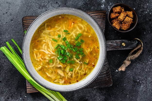 Zuppa di pollo fresca fatta in casa con noodle a tavola. sfondo nero. vista dall'alto.