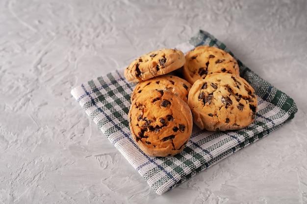Biscotti freschi fatti in casa con cioccolato su un tovagliolo su uno sfondo grigio