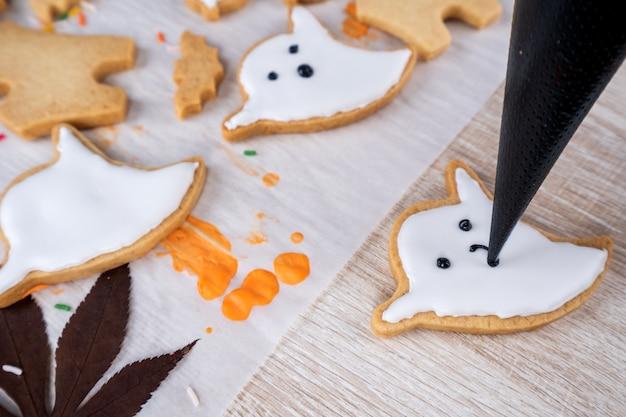 Dolce di halloween di decorazione fatta in casa fresca con fantasma, ragno strisciante, pipistrello, castello infestato e orribile bulbo oculare su fondo in legno, spazio di copia