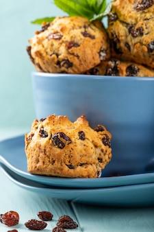 Muffin all'uvetta deliziosi fatti in casa freschi in tazza blu, senza zucchero. concetto di cibo sano