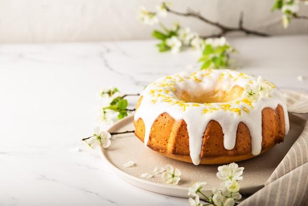 Torta al limone fresca fatta in casa decorata con glassa bianca e scorza su sfondo di marmo bianco