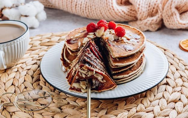 Frittelle fatte in casa fresche con mandorle, lamponi e caffè su sfondo bianco kithen. colazione accogliente