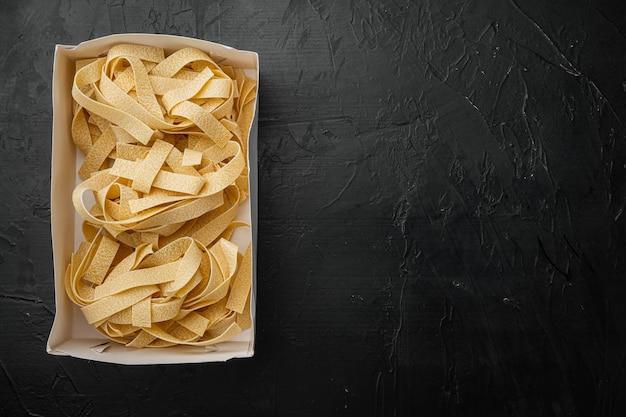 Set di pasta fresca fatta in casa, su sfondo nero tavolo in pietra scura, vista dall'alto piatta, con spazio copia per il testo