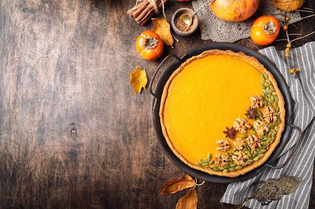 Torta di zucca fresca fatta in casa per il ringraziamento decorata con noci e semi al vassoio vintage su compensato rustico