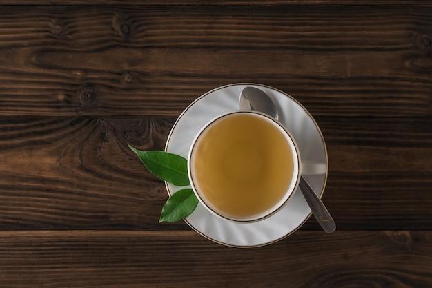 Tè fresco fatto in casa in un bicchiere bianco e piattino su un tavolo di legno. la vista dall'alto. una bevanda tonificante utile per la salute.