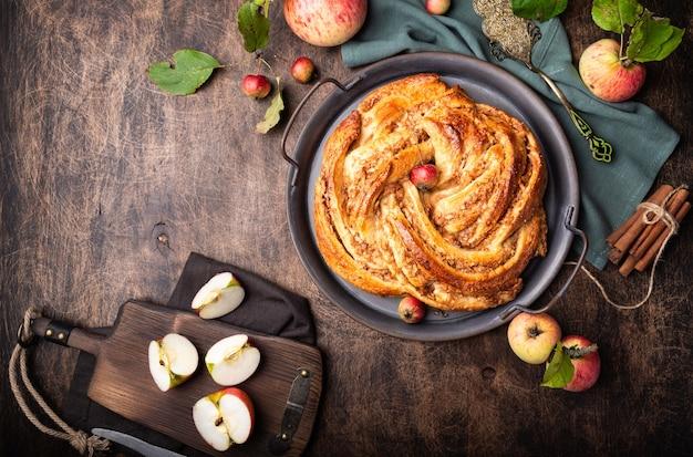 Torta contorta fresca fatta in casa con ripieno di mele e cannella nel vassoio vintage su fondo rustico in compensato. vista dall'alto.