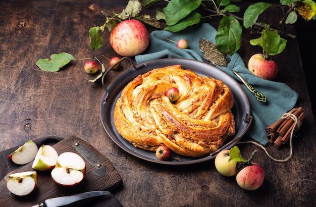 Torta contorta fresca fatta in casa con ripieno di mele e cannella nel vassoio vintage su compensato rustico.