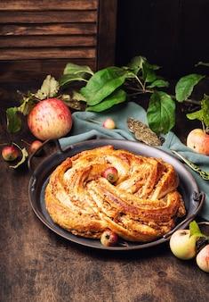 Torta contorta fresca fatta in casa con ripieno di mele e cannella nel vassoio vintage su compensato rustico
