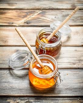 Miele fresco in un barattolo di vetro con un cucchiaio. su uno sfondo di legno.